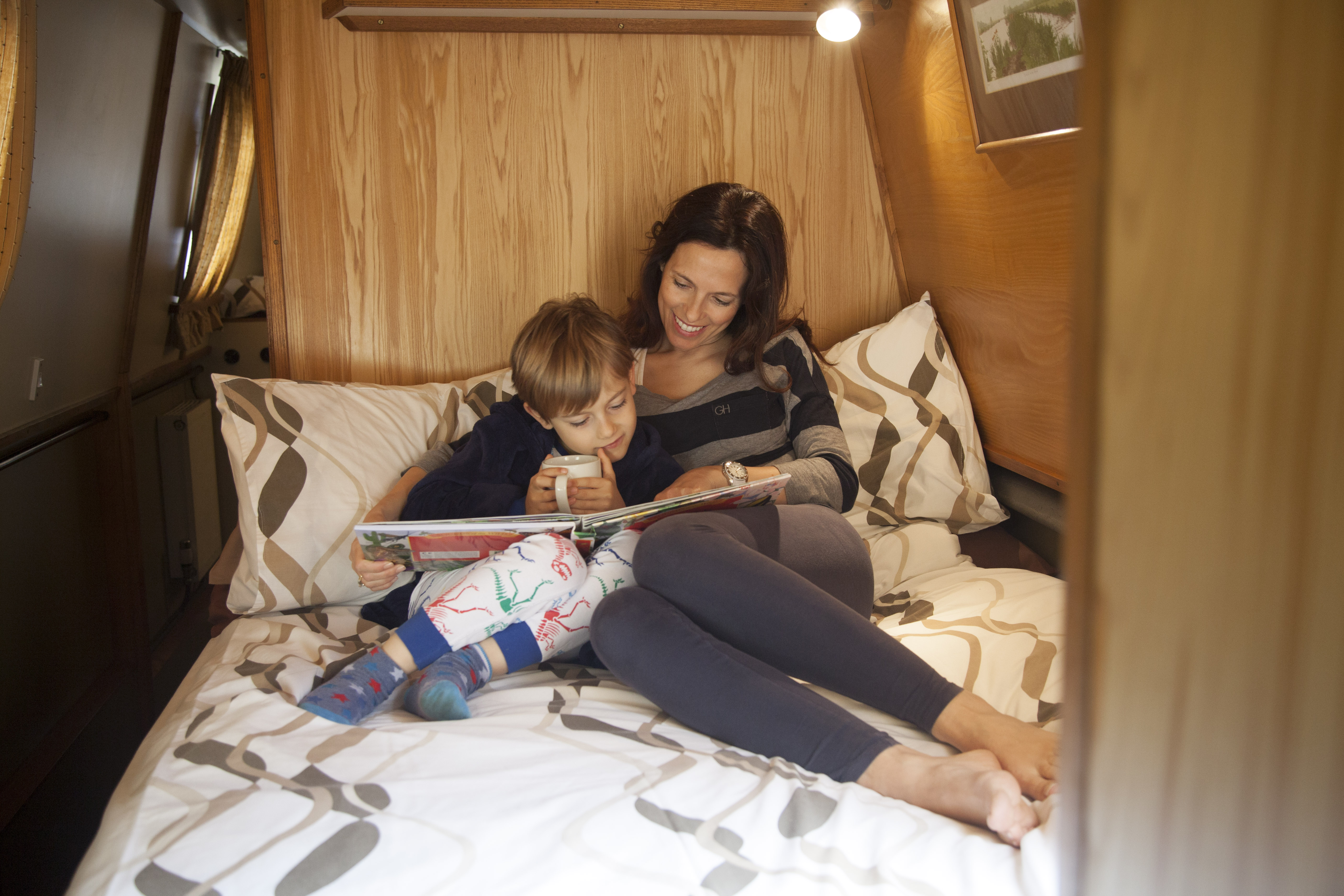 Mother reading book to child on board a UCC narrowboat