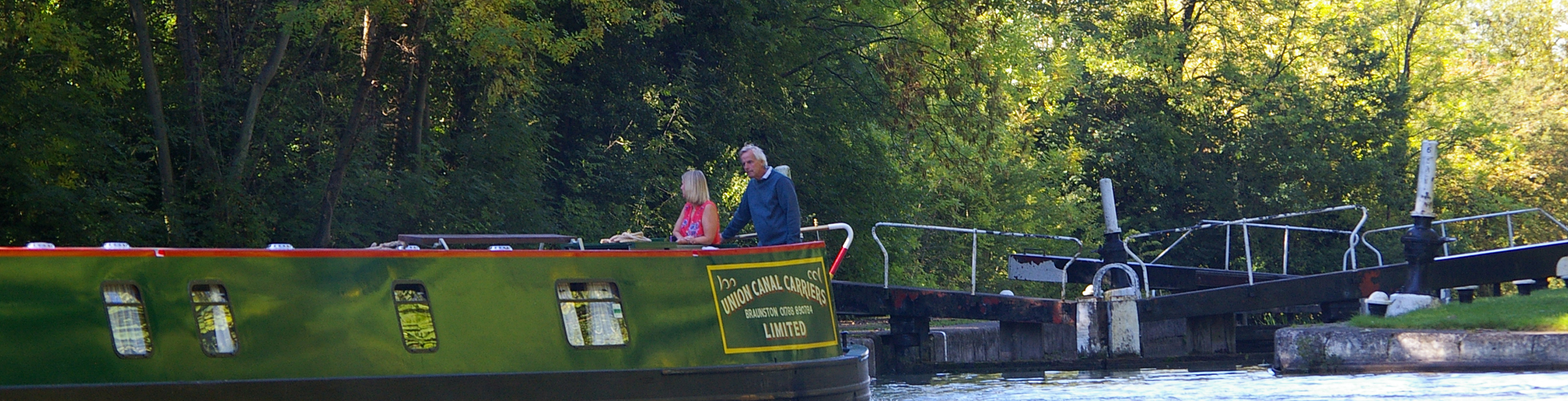 Narrowboat leaves a lock with family onboard