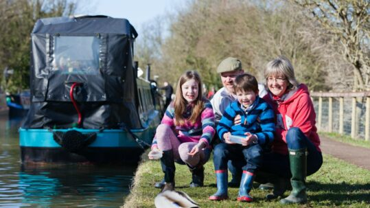 Family feeding ducks alongside canal